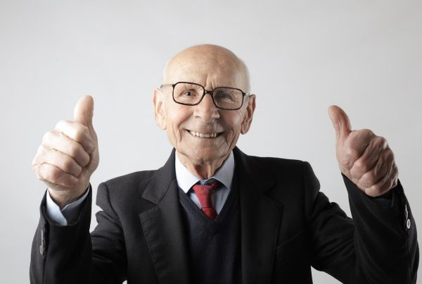 senior smiling and giving two thumbs up