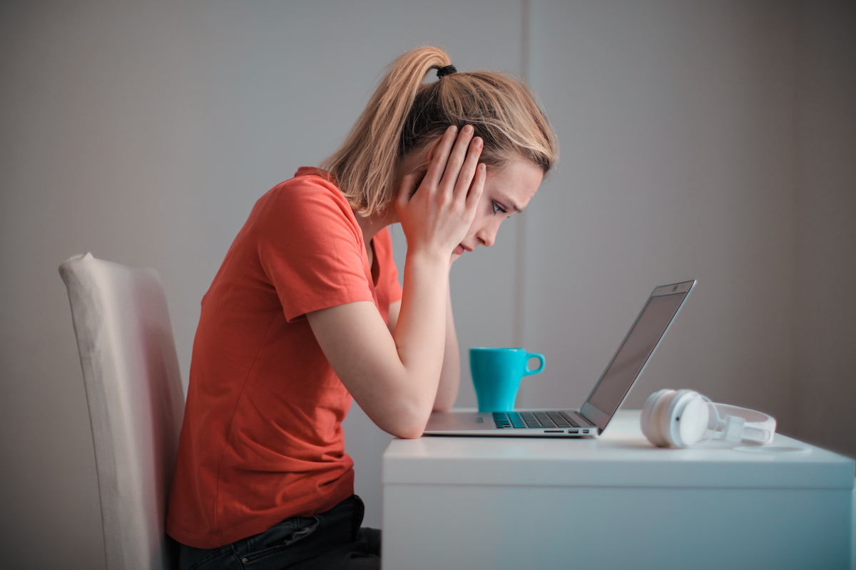 girl with a bad attitude sitting at her desk with laptop