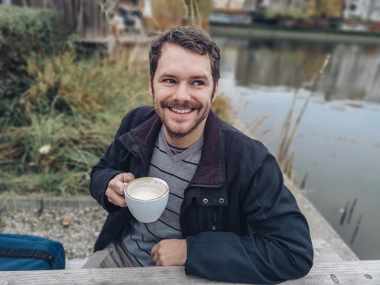 smiling man drinking coffee