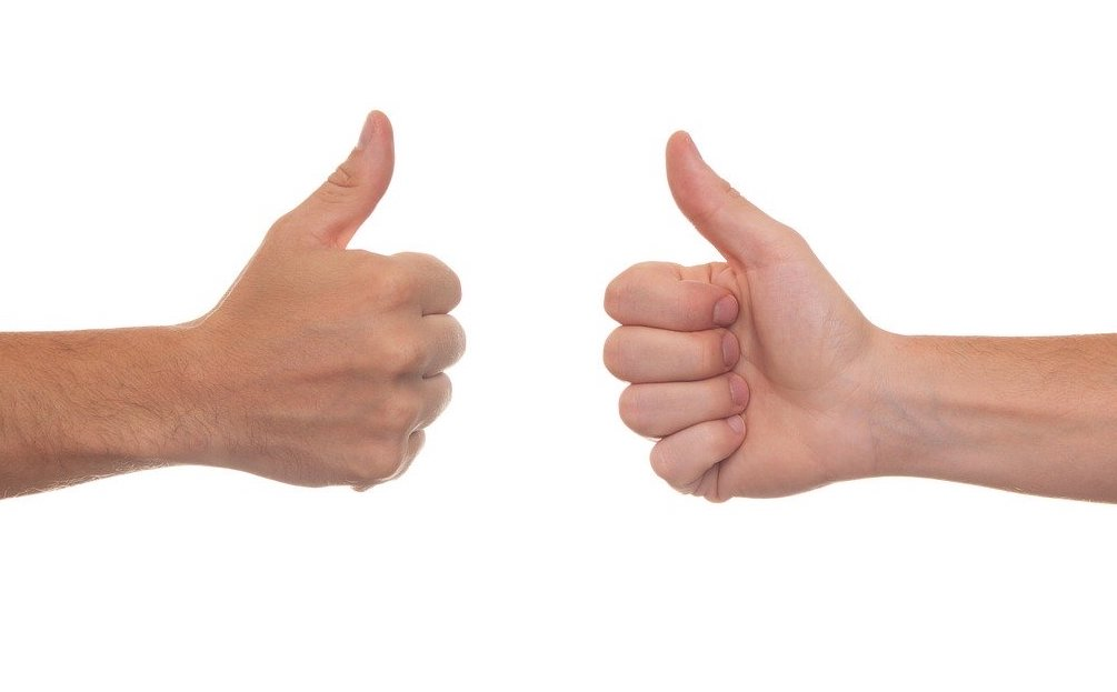 two hands facing each other with thumbs up