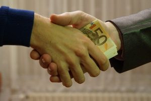 man giving money to another man by shaking his hand