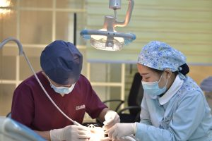 dentist with dental assistant examining patient's mouth under a light