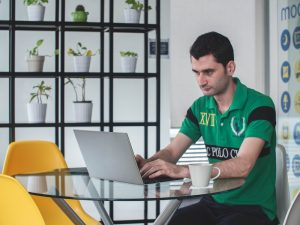 man sitting at table typing on computer or leaving an online review