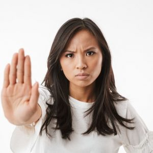 """woman putting up her hand as if to say """"no"""""""