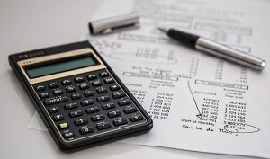 financial paper showing insurance with calculator and pen