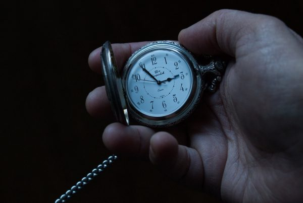 hand holding a pocket watch to communicate the idea of running late